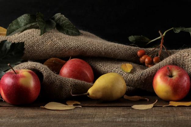 Arranjo de outono com maçãs e peras e folhas amarelas de outono em uma mesa de madeira marrom