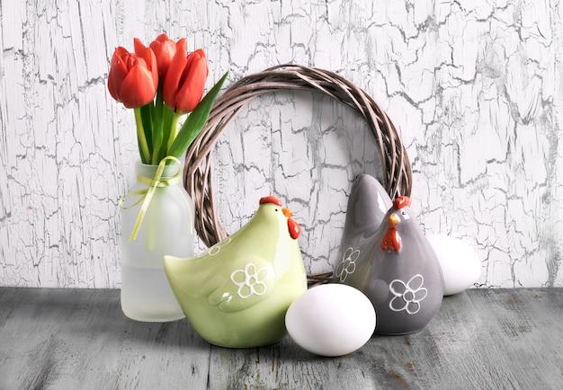 Arranjo de páscoa com coroa de madeira, tulipas vermelhas, galinhas e ovos de cerâmica