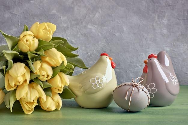 Arranjo de páscoa com monte de tulipas amarelas, galinhas de cerâmica e ovo de páscoa em cinza com cópia-espaço