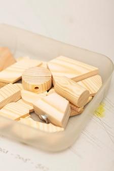 Arranjo de peças de madeira em caixa de plástico