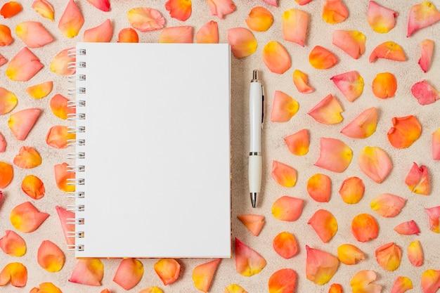 Arranjo de pétalas de rosa ao lado de um notebook