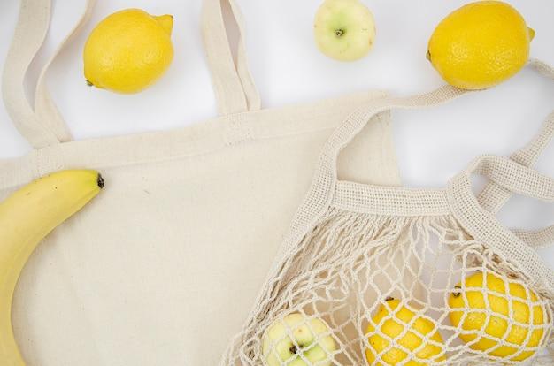 Arranjo de postura plana com frutas e saco de algodão
