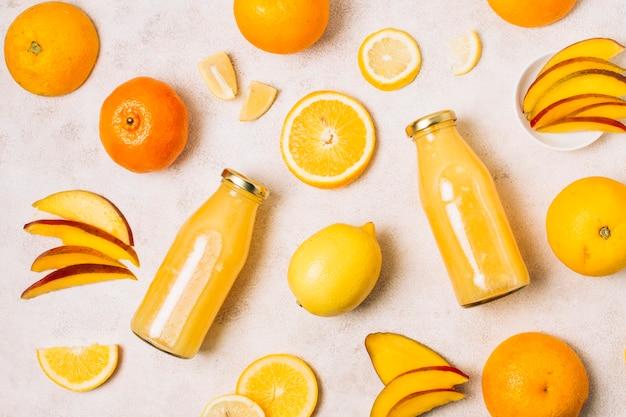 Arranjo de postura plana com frutas e smoothies de laranja