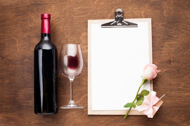 Arranjo de postura plana com vinho e prancheta