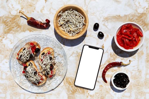 Arranjo de prato de gulas tradicional com smartphone