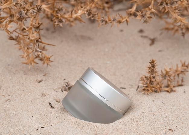 Arranjo de produtos para cuidados com a pele na areia