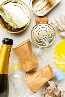 Arranjo de restos de comida desperdiçada em latas e champanhe