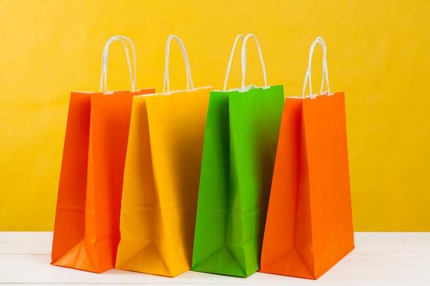Arranjo de sacolas de compras em fundo amarelo brilhante