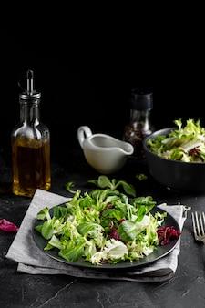 Arranjo de salada vista frontal com talheres escuros
