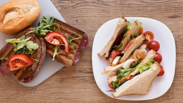 Arranjo de sanduíches frescos em fundo de madeira