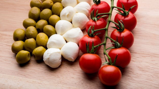 Arranjo de tomates vermelhos alegres; queijo; azeitonas sobre a superfície de madeira