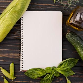 Arranjo de vegetais com bloco de notas vazio
