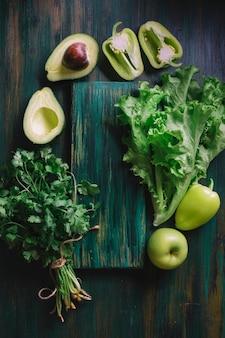 Arranjo de vegetais verdes e uma tábua de cortar