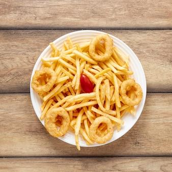 Arranjo de vista superior com batatas fritas e anéis de cebola