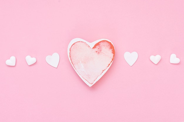 Arranjo de vista superior com biscoitos em forma de coração e fundo rosa
