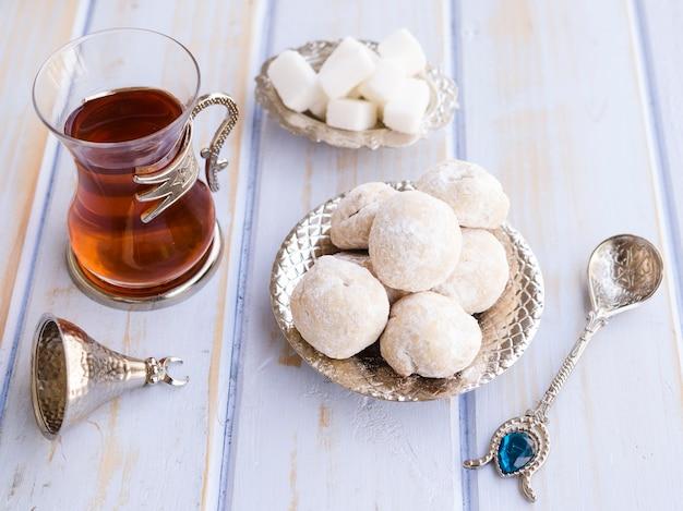 Arranjo de vista superior com chá, biscoitos e colher