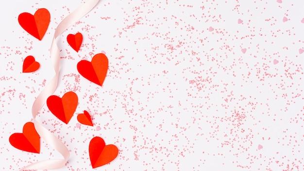 Arranjo de vista superior com corações vermelhos e fita