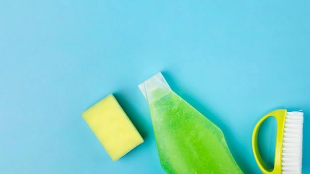 Arranjo de vista superior com detergente verde, esponja e escova