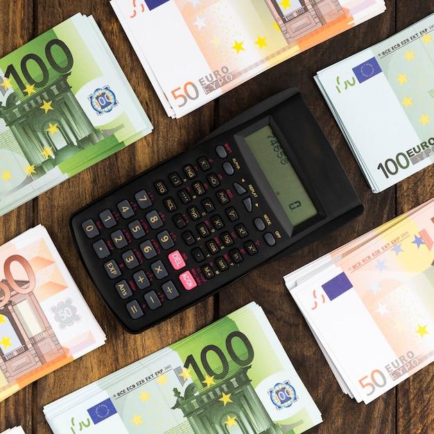 Arranjo de vista superior com dinheiro e calculadora de bolso