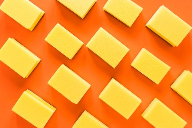 Arranjo de vista superior com esponjas em fundo laranja