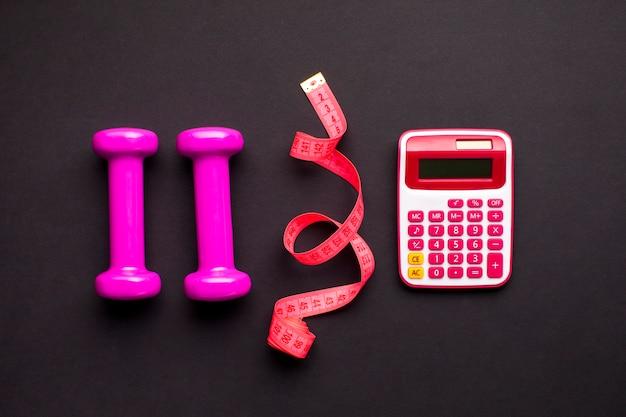 Arranjo de vista superior com halteres e calculadora