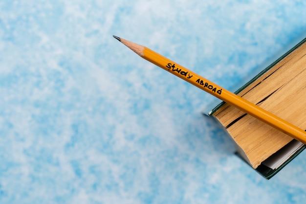 Arranjo de vista superior com livro e lápis com mensagem