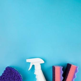 Arranjo de vista superior com produtos de limpeza em fundo azul
