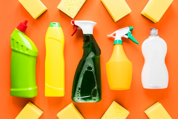 Arranjo de vista superior com produtos de limpeza em fundo laranja