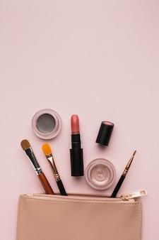 Arranjo de vista superior com produtos de maquiagem com bolsa de beleza
