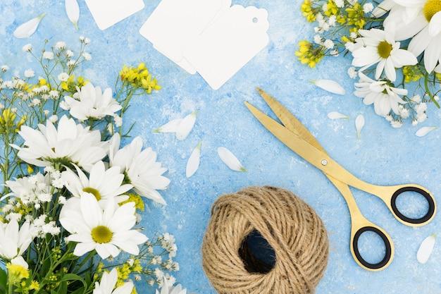 Arranjo de vista superior com tesoura e flores