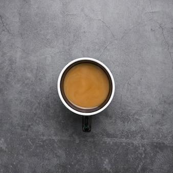 Arranjo de vista superior com uma xícara de café sobre fundo de estuque