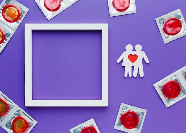 Arranjo do conceito de contracepção com preservativos vermelhos e moldura vazia