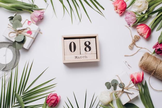 Arranjo festivo: caixas com presentes, fitas, calendário e tulipas com folha de palmeira.