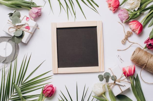 Arranjo festivo: caixas com presentes, fitas, quadro-negro e tulipas com folha de palmeira.
