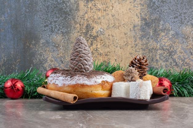 Arranjo festivo de doces em uma travessa de mármore.