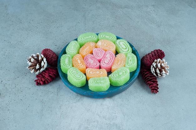 Arranjo festivo de pinha e um prato de marmeladas em mármore.