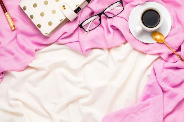 Arranjo flatlay bonito com uma xícara de café preto com colher, copos, planejador pontilhado e caneta na cama.