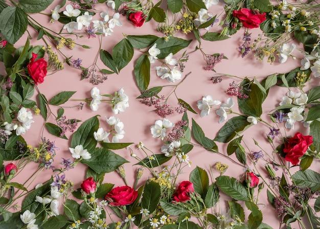 Arranjo floral com diferentes flores frescas, folhas e galhos em uma superfície rosa
