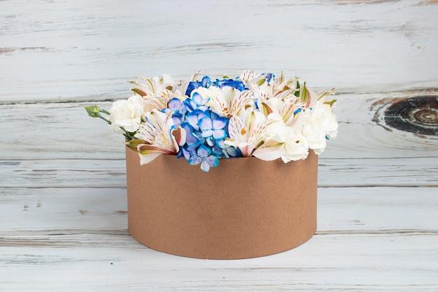 Arranjo floral com hortênsias azuis em caixa de papelão reciclável