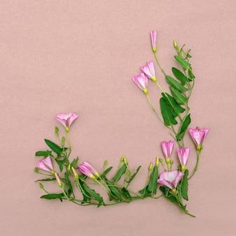 Arranjo floral de flores silvestres rosa em um fundo rosa. cartão com lugar para design.