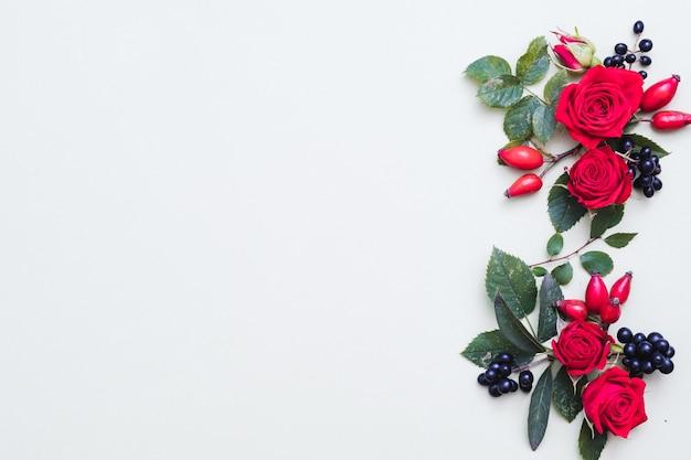 Arranjo floral de outono bagas vermelhas e pretas caem, folhas verdes e rosas em branco