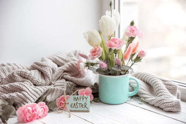 Arranjo floral de páscoa com flores naturais e a inscrição feliz páscoa no cartão.