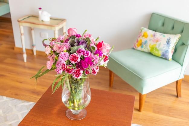 Arranjo floral de rosas e cravos que decoram a sala da casa