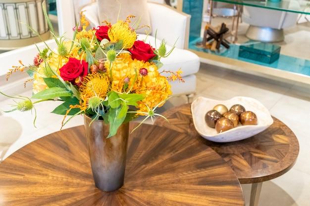 Arranjo floral de rosas e cravos que decoram a sala de estar da casa