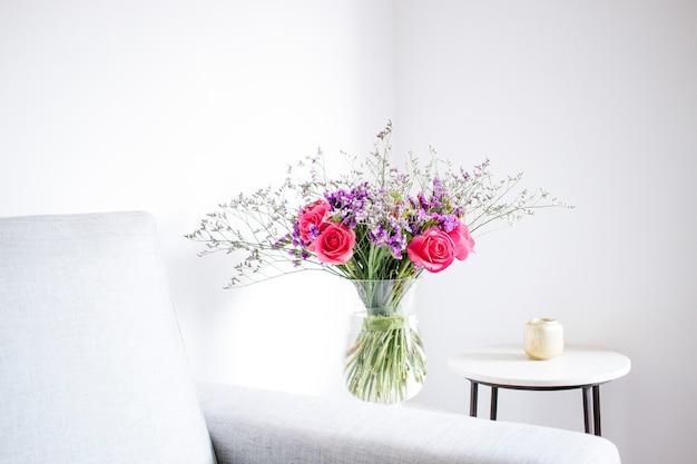 Arranjo floral de rosas e limonios decorando a sala de estar da casa