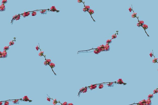 Arranjo floral feito com ramos de flores rosa contra superfície azul pastel