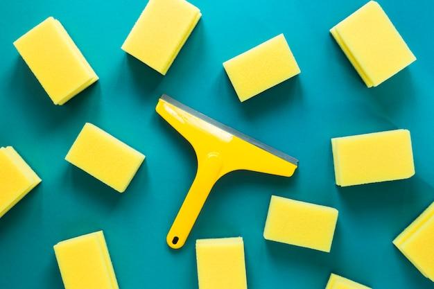 Arranjo liso leigo com esponjas amarelas sobre fundo azul
