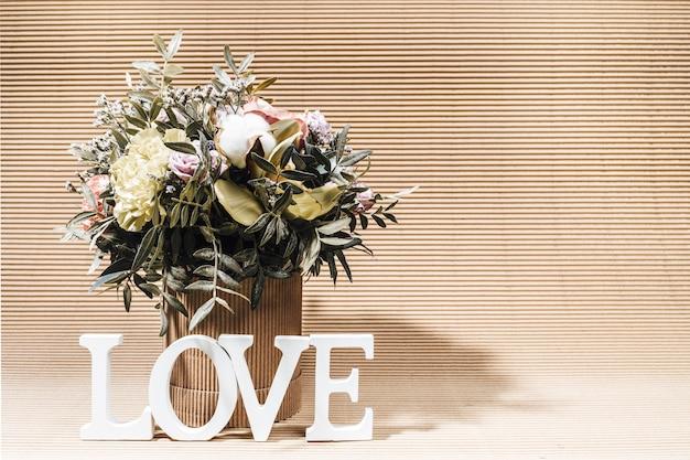 Arranjo moderno ecológico com buquê de flores em vaso de papelão diy e letras brancas amor em fundo de caixa bege com sombras.