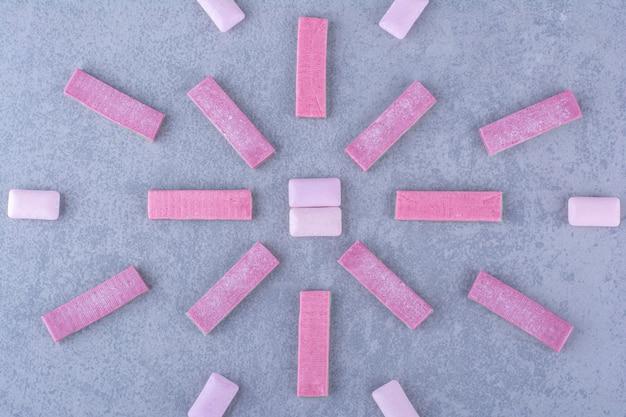 Arranjo multilinear de tiras de chiclete e comprimidos na superfície de mármore