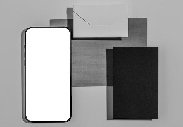 Arranjo organizado de elementos de papelaria com tela em branco do smartphone